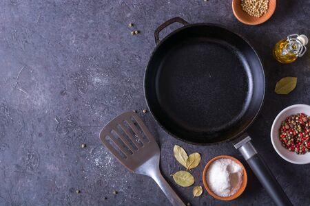 Padella e uova. Vista ravvicinata degli ingredienti dell'uovo fritto e di una padella. Padella vuota in ghisa, uova, sale, pepe, olio e prezzemolo su sfondo nero per la cottura di uova fritte. Archivio Fotografico