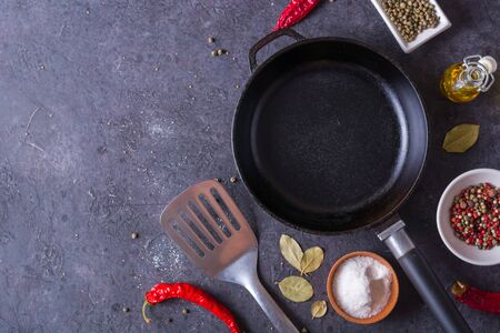 Frying pan and eggs. Close up view of ingredients of fried egg and a frying pan. Empty cast iron pan, eggs, salt, pepper, oil and parsley on black background for cooking fried eggs. 版權商用圖片
