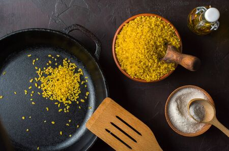 Bulgur on a dark background. Preparation for roasting. Useful organic food for breakfast or diet. Natural fabrics and earthenware. Copy space.