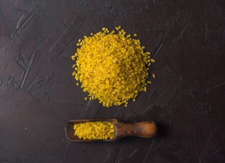 Bulgur lying in a heap on a dark background. Useful organic food for breakfast or diet. Plenty of room for text. Copy space.