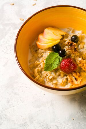 Morning oatmeal for breakfast. Early morning and healthy diet food. Proper nutrition. White stone background. Plenty of space for text Stok Fotoğraf