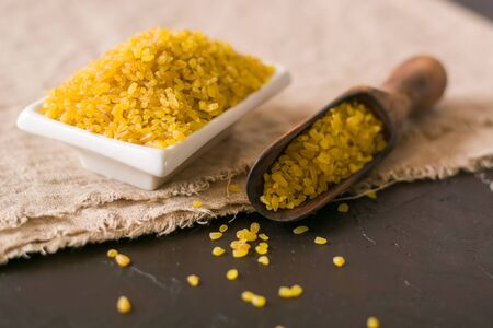 Bulgur on a dark background. wholesome organic food for breakfast or diet. Natural fabrics and earthenware. Copy space.