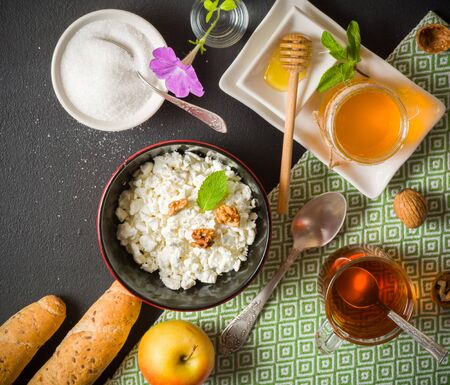 Fresh white cottage cheese in a bowl on the table. Tasty and healthy breakfast. dark stone surface. View from above. A lot of space for text