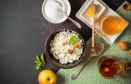 Fresh white cottage cheese in a bowl on the table. Tasty and healthy breakfast. dark stone surface. View from above. A lot of space for text.