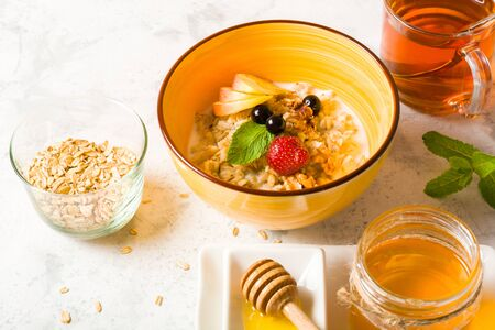Morning oatmeal for breakfast. Early morning and healthy diet food. Proper nutrition. White stone background. Plenty of space for text.
