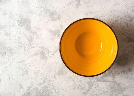 Empty yellow ceramic bowl on a light stone background. Stok Fotoğraf