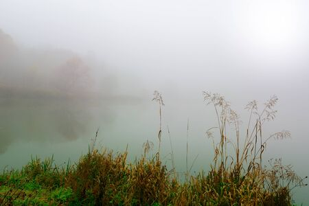 Morning fog on the lake in the fall. Mystical and mysterious weather. Gray autumn natural background.