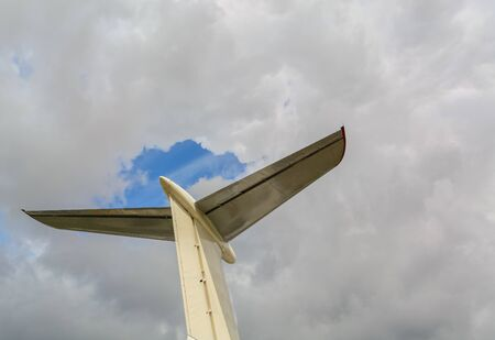 Airplane wing and stabilizer on a cloud background. Background for articles about aviation, travel or business trips