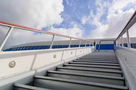 Ladder for departing passengers near the plane. Against the background of blue sky and clouds. Stairway to Heaven