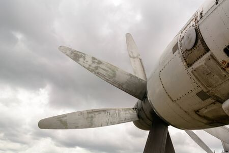 Part of the fuselage of the old military plane with the propeller closeup against the background of an empty and gray sky Imagens