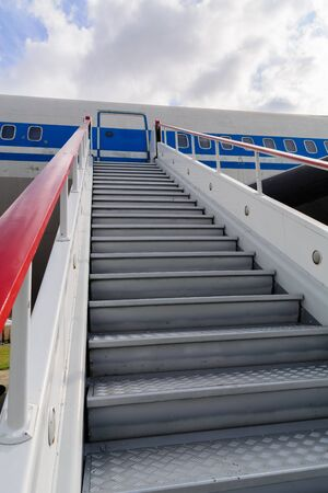 Ladder for departing passengers near the plane. Against the background of blue sky and clouds. Stairway to Heaven.