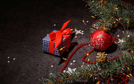 Background or preparation for a postcard. Christmas tree branches and decorations on a dark background. A Christmas present. Stock fotó - 159893173