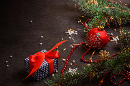 Background or preparation for a postcard. Christmas tree branches and decorations on a dark background. A Christmas present. Stock fotó
