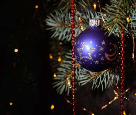 A blue glass ball on a Christmas tree. Dark background. Stock fotó