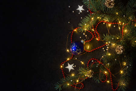 Christmas background for postcards. LED garland on a dark background. Christmas tree branches. Stock fotó