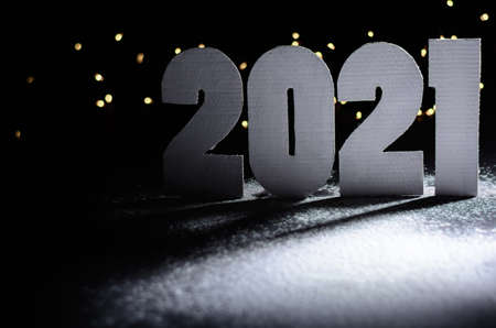Christmas dark background with cardboard numbers 2021. Blurred lights garland in the background. Its snowing.