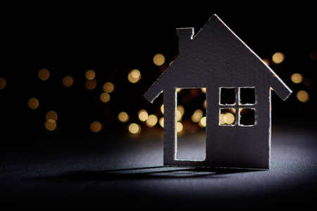 Small cardboard house on a dark winter background.