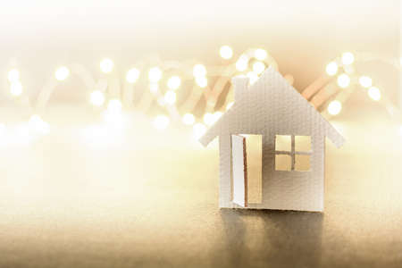 Small cardboard house on a winter background.