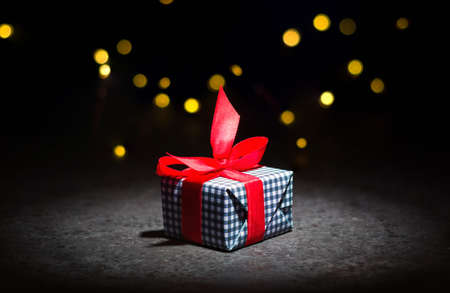 A box with a gift on a dark background. Red tape. Stock fotó
