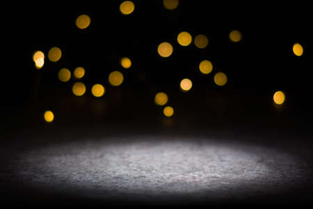 Dark background and bright blurred lights from behind. illuminated place in the foreground. Stock fotó