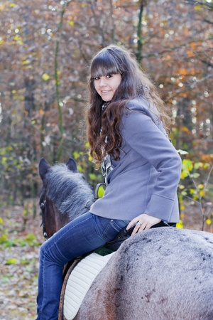 Young brunette girl on horseback in autumn photo