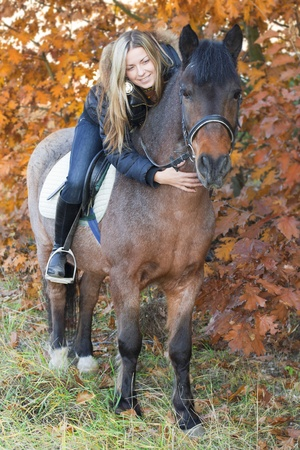 Young girl on horseback stroking a horse. Autumnal background Stock Photo