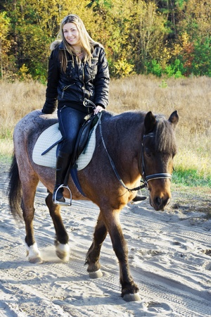 black cowgirl: Young girl on horseback over autumnal background Stock Photo