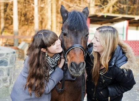 Two happy girls holding a horse and smiling