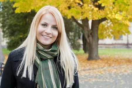 秋の背景の上の微笑の若いブロンドの女性の肖像画
