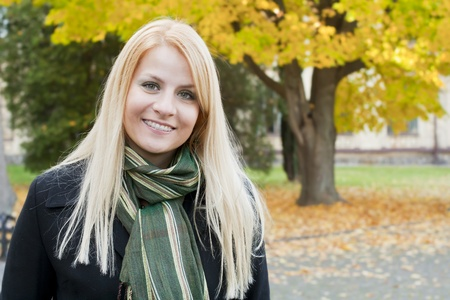 Portrait of smiling young blond woman over autumnal background Stock Photo