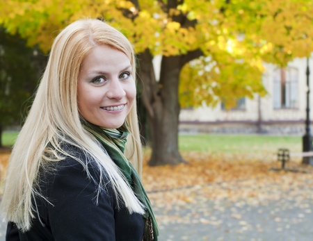 Portrait of smiling young blond woman over autumnal background photo