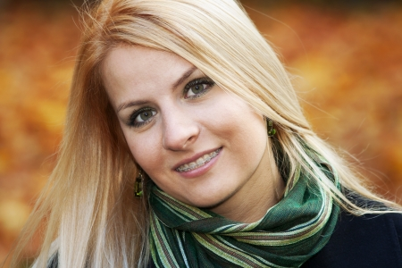 Portrait of smiling young blond woman over yellow autumn leaves, 25-30 years old photo