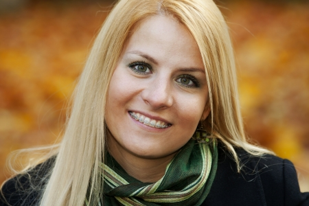 cute braces: Portrait of smiling young blond woman over autumnal background Stock Photo