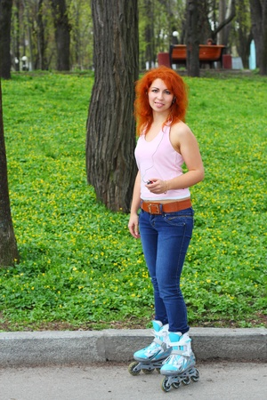 Ginger girl on roller skates listening to music in the park Stock Photo - 13330579