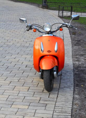 Orange scooter parked in the park photo