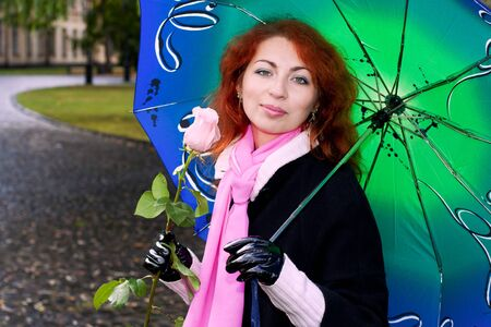 Portrait of a young  ginger girl holding a pink rose under umbrella photo