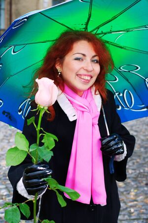 Portrait of a young  ginger girl under umbrella giving a pink rose photo