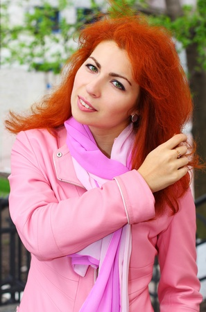 Portrait of a young pretty red haired girl combing her hair with her hand Stock Photo - 13345693