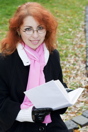 Young smiling red haired lady wearing glasses holding a book. The girl looks like a teacher or a student. photo