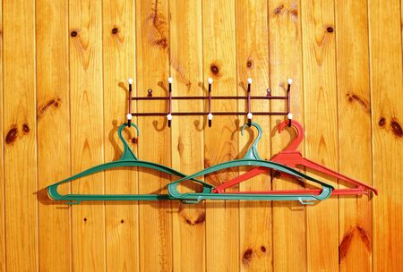 Clothes hangers on wooden wall of the hotel photo
