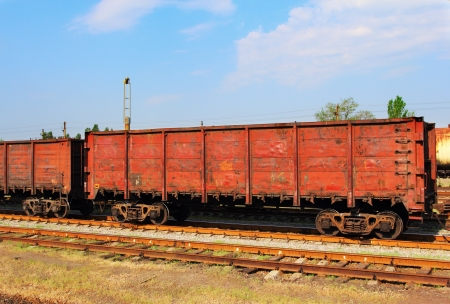 Red cargo wagons on railway over the blue sky Stock Photo