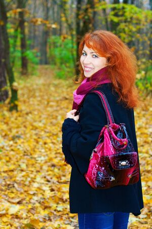 Red headed girl on her way through the forest with her bag on in autumn photo