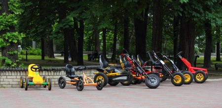 a two wheeled vehicle: Many four wheeled bicycles on pavement on the park