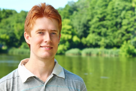 Portrait of a young red haired man over rural landscape photo
