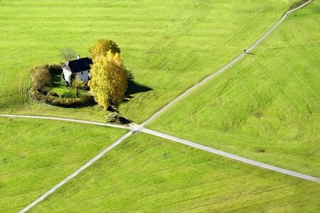 The crossroads on the greenish grass and a cottage in Salzburg, Austria