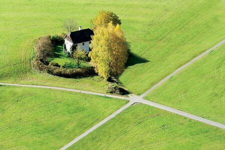 intersect: The crossroads on the greenish grass and a cottage in Salzburg, Austria