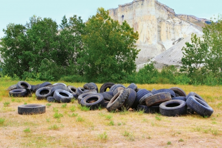 Pile of used wheels on the grass Stock Photo