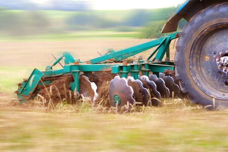 plough machine: Tractor ploughing the field. Motion blur was done for effect to emphasize speed