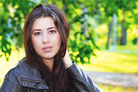 Portrait of a young pretty brunette girl in the park Stock Photo - 15829599