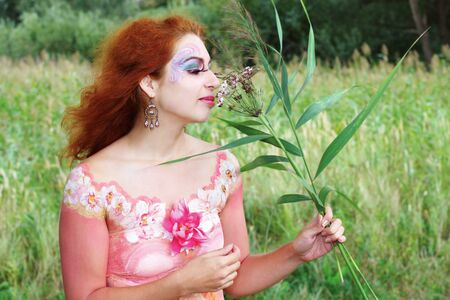 Red haired girl with body art smelling the flower photo